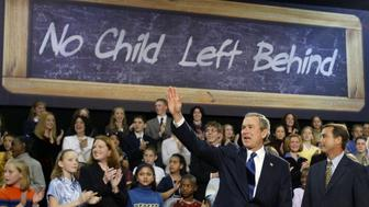 "U.S. President George W. Bush, accompanied by Rep. John Boehner (R-Oh), waves to supporters prior to signing the ""No Child Left Behind"" education bill during a ceremony at Hamilton High School in Hamilton, Ohio January 8, 2002. The education bill is the centerpiece of Bush's domestic policy agenda. REUTERS/Win McNamee  WM/HB"