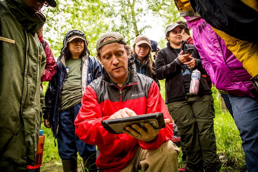 A hydrologist from National Park Services teaches volunteers about the technology used to determine landforms.