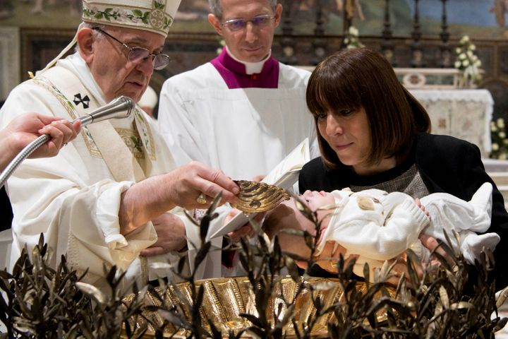 Pope Francis baptizes an infant during a solemn mass in the Sistine Chapel at the Vatican January 7, 2018.