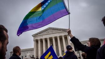 WASHINGTON, DC - DECEMBER 5: Hannah Flood, an American University student from Maine, holds her rainbow flag high outside the Supreme court, which is hearing arguments in the Masterpiece Bakery discrimination case on December, 05, 2017 in Washington, DC. (Photo by Bill O'Leary/The Washington Post via Getty Images)