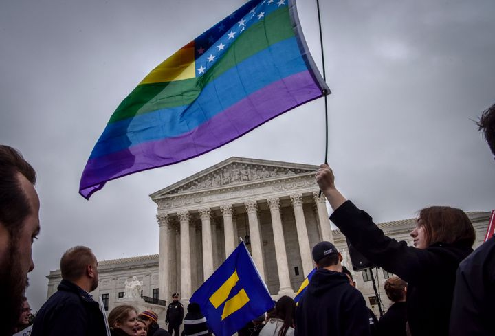 Hannah Flood, an American University student from Maine, holds her rainbow flag high outside the Supreme Court on Dec. 5