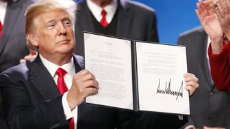 U.S. President Donald Trump displays a signed executive order, expanding rural broadband access to towers on federal lands, during the annual American Farm Bureau Federation conference in Nashville, Tennessee, U.S., on Monday, Jan. 8, 2018. Trump said lower taxes and deregulation will rev up the rural economy in a partisan speech geared toward a much broader audience than the farmers gathered to hear him. Photographer: Luke Sharrett/Bloomberg via Getty Images