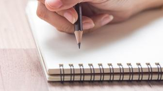 Business women hands working writing on notebook on wooden desk, lighting effect