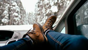 Photo of a female boots, up in the car's dashboard, on a road trip - ready for a next winter adventure