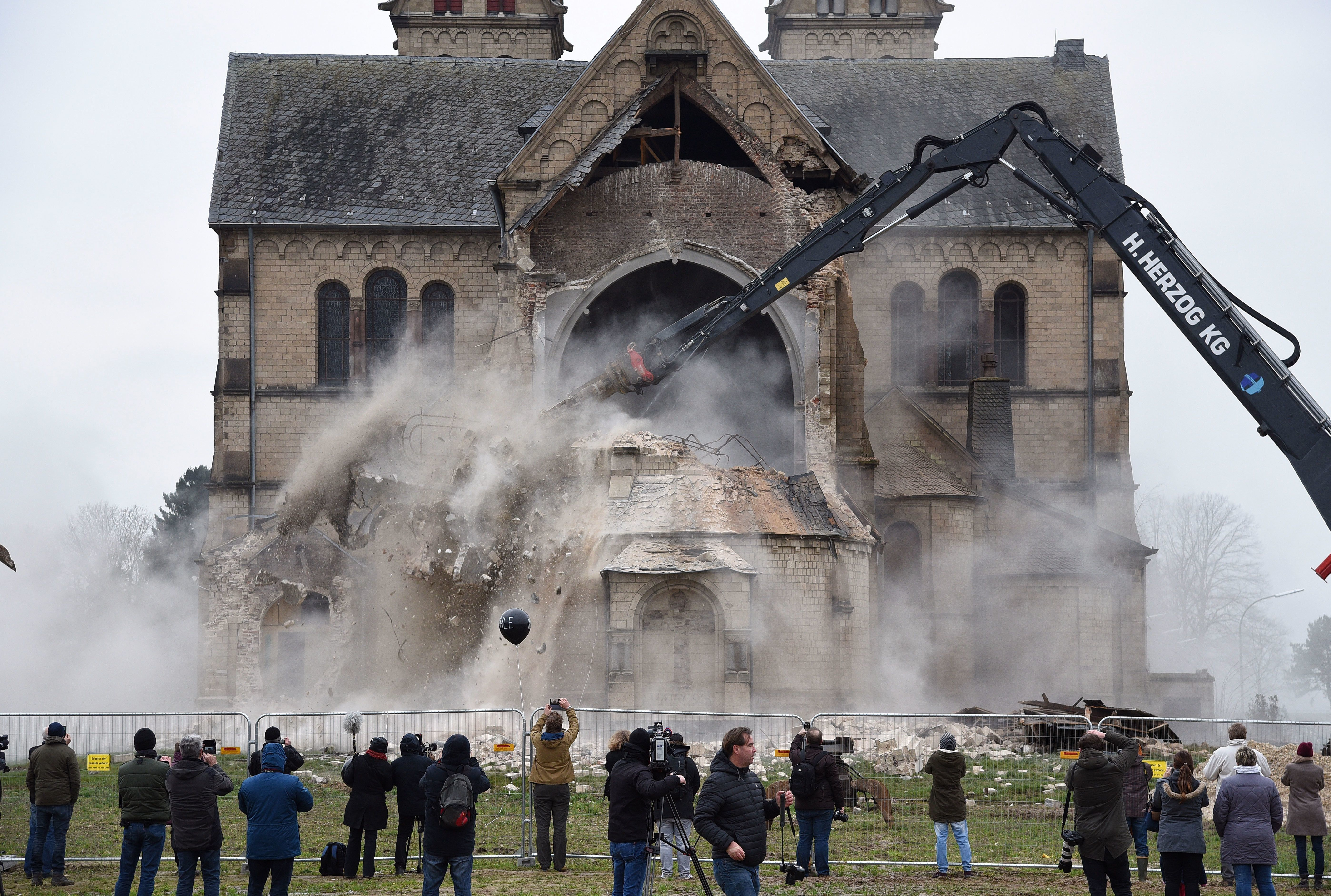 Spectators and journalists look on as St. Lambertus church in Erkelenz-Immerath, western Germany, is...