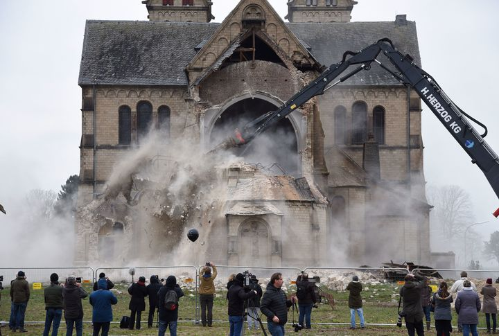 Spectators and journalists look on as St. Lambertus church in Erkelenz-Immerath, western Germany, is demolished on Jan. 8, 2018.