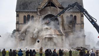 Spectators and journalists look on as the desacralized St Lambertus church in Erkelenz-Immerath, western Germany, is being demolished on January 8, 2018, in order to make possible brown coal surface mining. Residents from the village of Immerath were relocated previously, as the area is to be exploited by German energy supplier RWE Power in an extension of their Tagebau Garzweiler open pit lignite mine. / AFP PHOTO / dpa / Henning Kaiser / Germany OUT        (Photo credit should read HENNING KAISER/AFP/Getty Images)