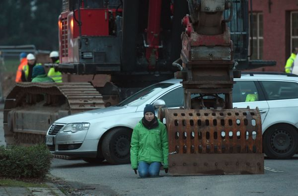 A Greenpeace activist protesting against coal is chained to an excavator shovel in front of the St. Lambertus church.