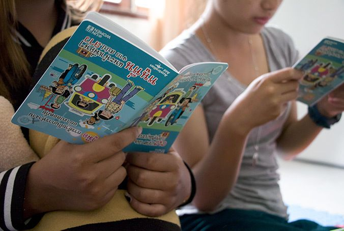 Two young women read the Safe Migration Booklet at the shelter for victims of trafficking in Vientiane, Laos. They had worke