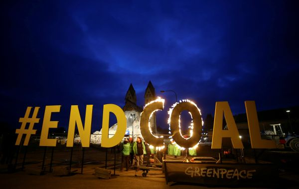 "Greenpeace activists light a protest banner reading ""#ENDCOAL"" with fire as the St. Lambertus church is demolished for the ex"