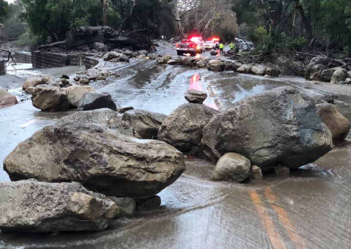Heavy rainfall over areas scorched by wildfires late last year triggered boulders and mud running into streets.