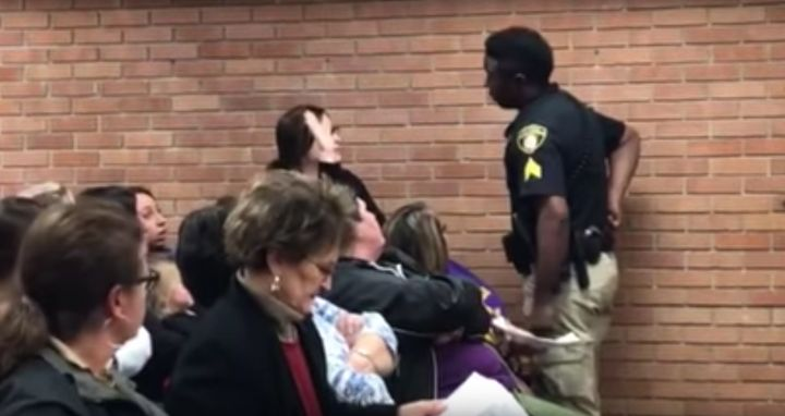 A woman identified as middle school teacher Deyshia Hargrave is confronted by a law enforcement officer during a school board