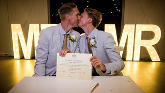 Australian Commonwealth Games sprinter Craig Burns (L) and partner Luke Sullivan (R) kiss as they hold their wedding certificate after their marriage ceremony at Summergrove Estate, New South Wales on January 9, 2018.  Australia officially become the 26th country to legalise same-sex marriage after the law was passed on December 9, 2017, with the overwhelming backing of the Federal Parliament. / AFP PHOTO / Patrick HAMILTON        (Photo credit should read PATRICK HAMILTON/AFP/Getty Images)
