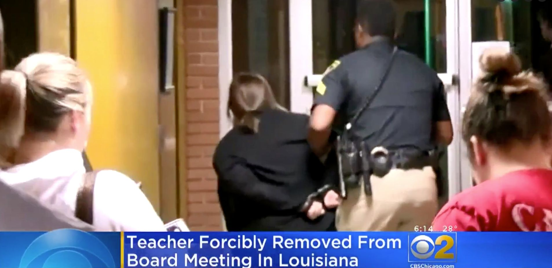 Teacher Deyshia Hargrave is seen being removed from the building in handcuffs after questioning a superintendent's pay raise