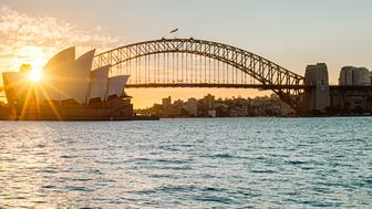 [UNVERIFIED CONTENT] Sydney Opera House and Harbour Bridge taken from Mrs. Macquarie's chair during golden hour. Backlit shot with a sun star burst.