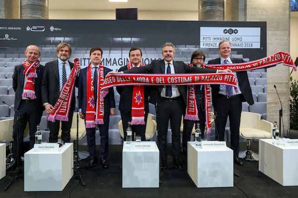 The opening ceremony of Pitti Uomo 93 - the speakers holding the giveaway scarf featuring the Museum of Costume and Fashion a