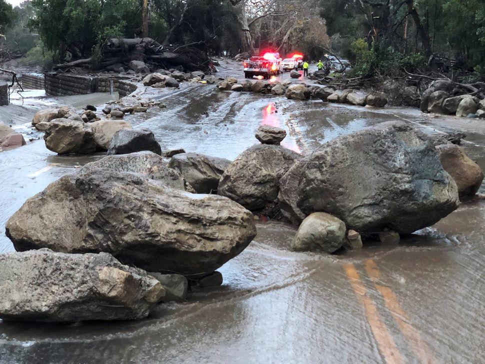 Boulders block a road after a mudslide.