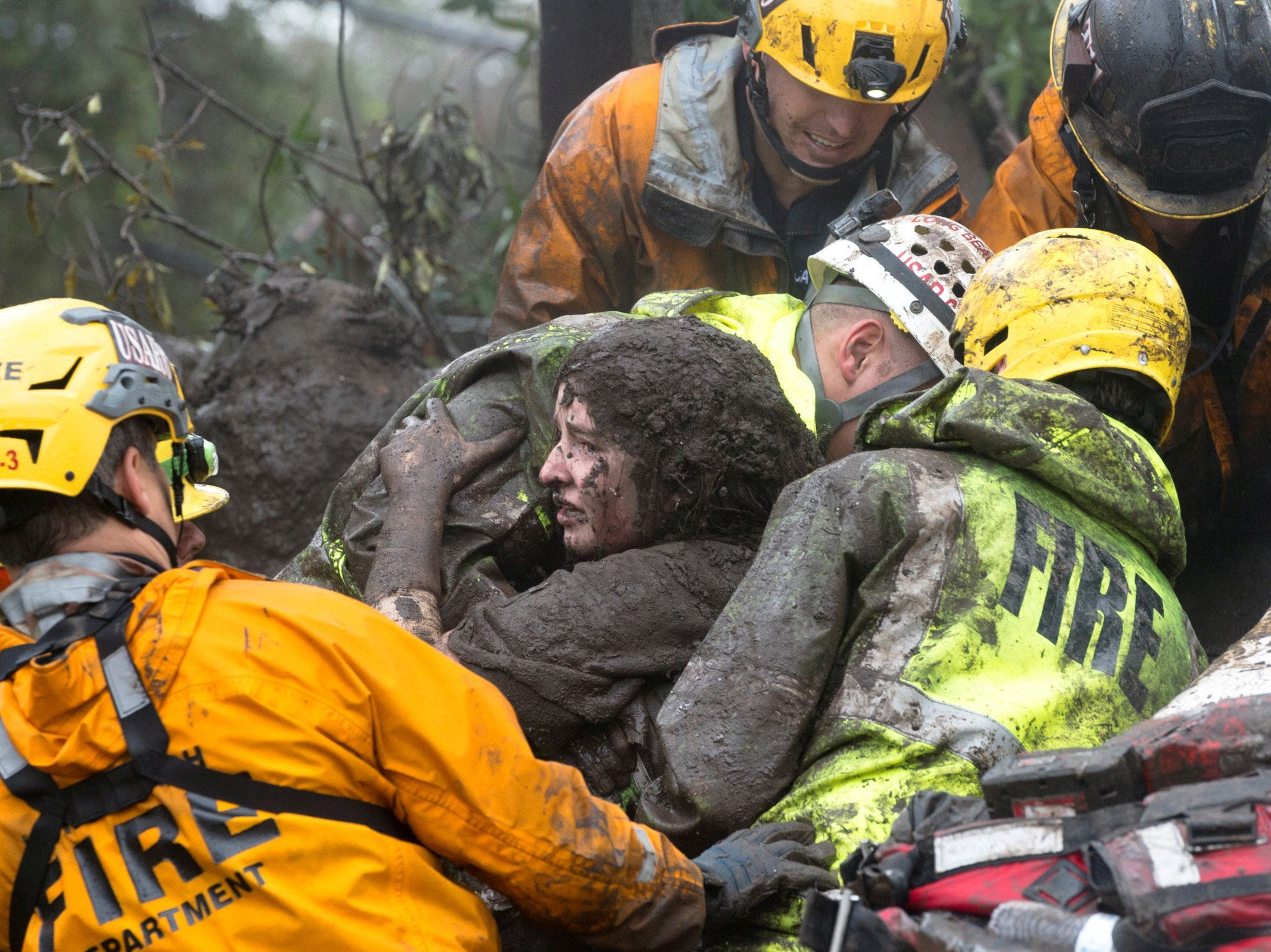 Emergency personnel carry a woman rescued from a collapsed house after a mudslide.