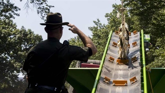 A New York State Environmental Conservation officer salutes as an ivory sculpture rolls into a crusher. The state is one of s