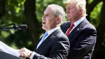 Scott Pruitt, administrator of the Environmental Protection Agency (EPA), left, speaks while U.S. President Donald Trump listens during an announcement in the Rose Garden of the White House in Washington, D.C., U.S., on Thursday, June 1, 2017. Trump announced the U.S. would withdraw from the Paris climate pact and that he will seek to renegotiate the international agreement in a way that treats American workers better. Photographer: T.J. Kirkpatrick/Bloomberg via Getty Images