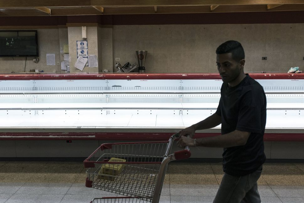 A customer pushes a shopping cart past an empty meat counter at a grocery store in Caracas, Venezuela, on Jan. 9, 2018. Horde