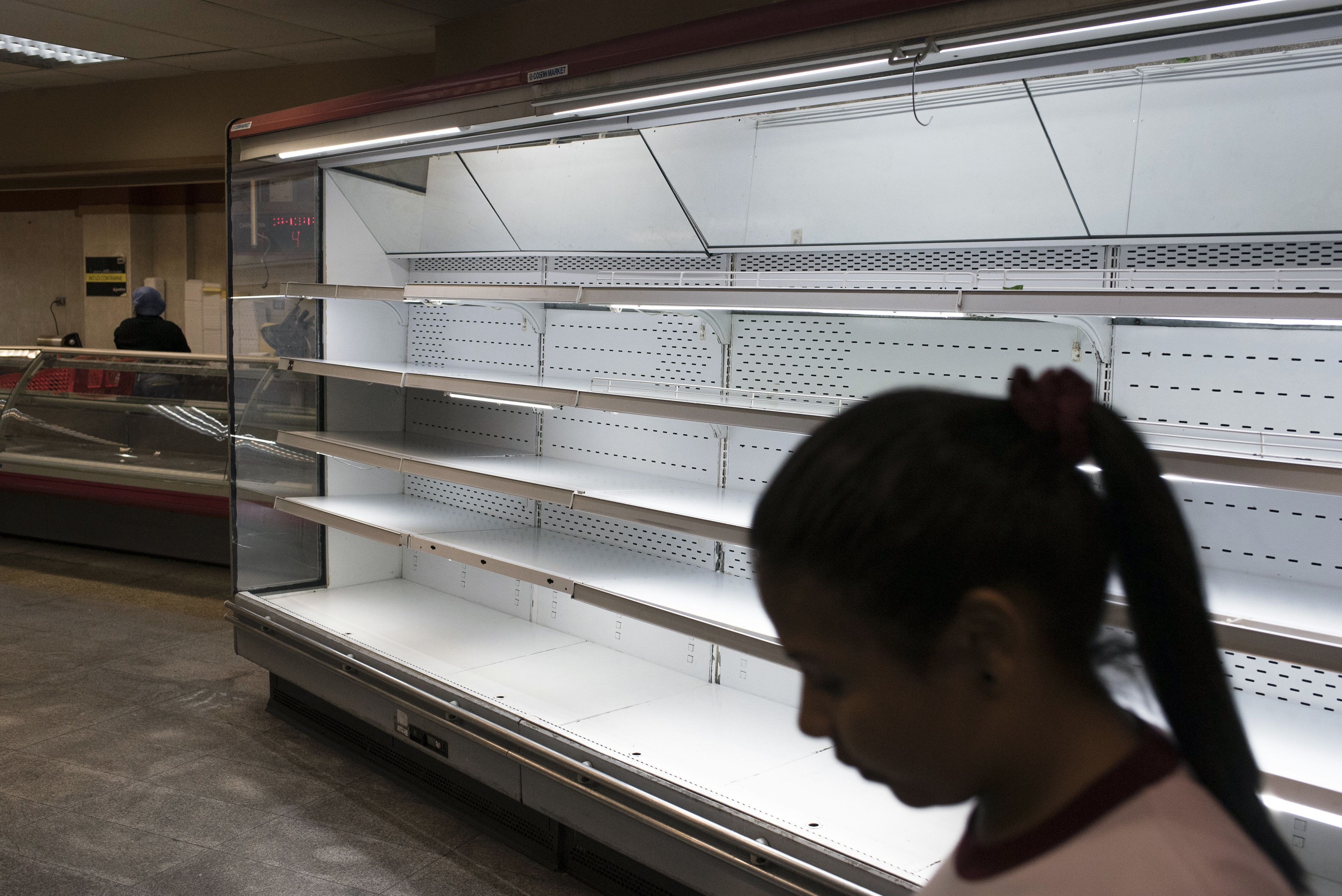 A customer passes empty shelves at a grocery store in Caracas, Venezuela, on Tuesday, Jan. 9, 2018. Hordes of desperate shoppers emptied supermarkets and bodegas last week after President Nicolas Maduro ordered hundreds of grocery stores slash their prices in the latest attempt to put a lid on hyperinflation. Photographer: Carlos Becerra/Bloomberg via Getty Images