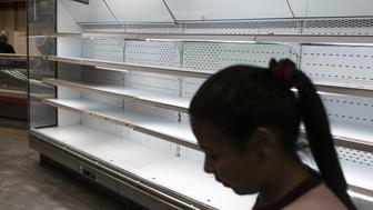 A customer passes empty shelves at a grocery store in Caracas, Venezuela, on Tuesday, Jan. 9, 2018. Hordes of desperate shoppers emptied supermarkets and bodegas last week after PresidentNicolas Maduroordered hundreds of grocery stores slash their prices in the latest attempt to put a lid on hyperinflation. Photographer: Carlos Becerra/Bloomberg via Getty Images
