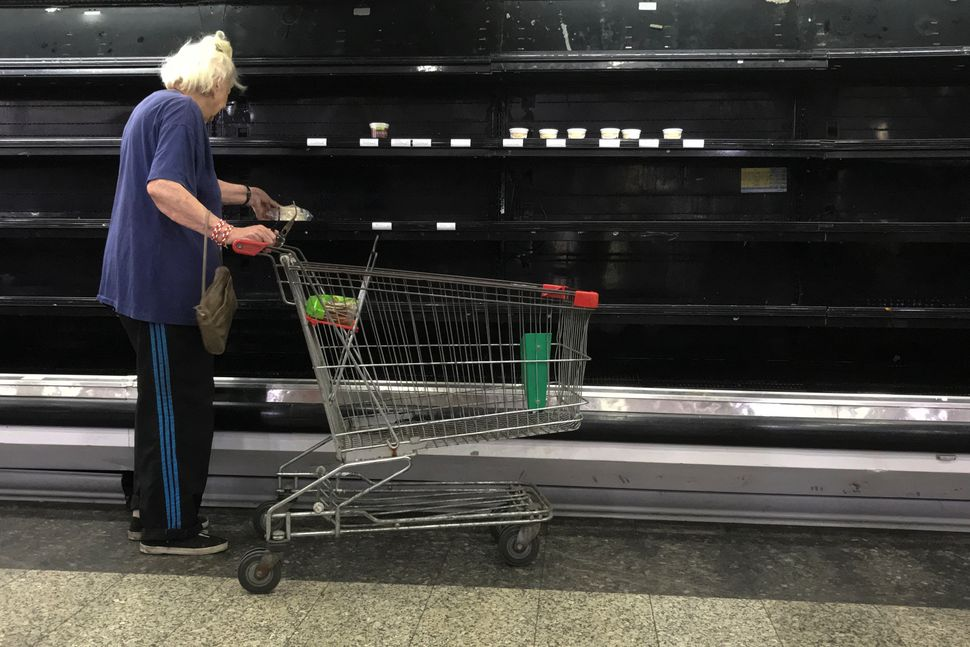 A woman selects goat cheese from near-empty shelves.