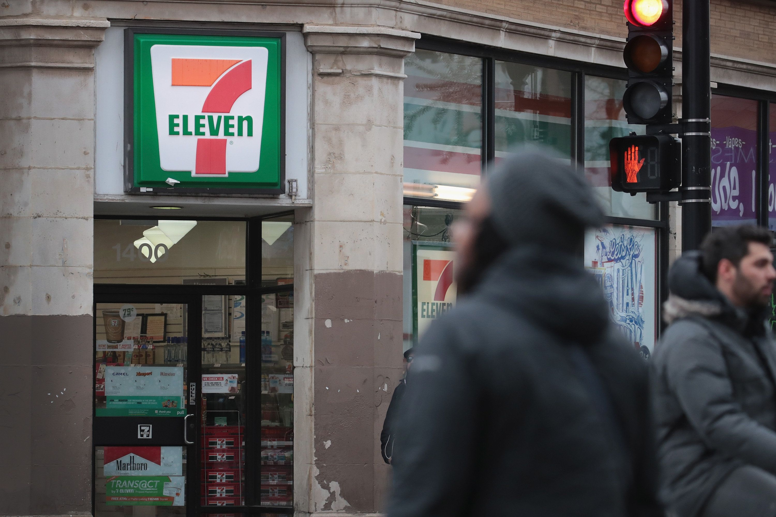 CHICAGO, IL - JANUARY 10:  Pedestrians walk past a 7-Eleven store on January 10, 2018 in Chicago, Illinois. Immigration officials raided nearly 100 7-Eleven stores across the country this morning checking the immigration status of store employees.  (Photo by Scott Olson/Getty Images)