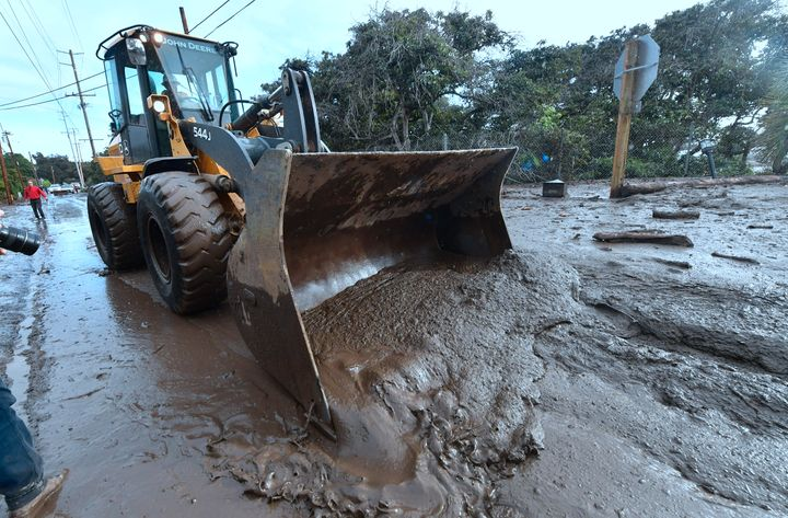 A bulldozer clears mud off the road near a flooded section of U.S. 101 near the San Ysidro exit in Montecito, California, on