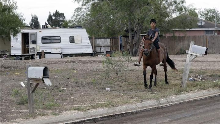A boy rides a horse through a <em>colonia</em> near Alamo, Texas. The makeshift settlements are among the areas where countin