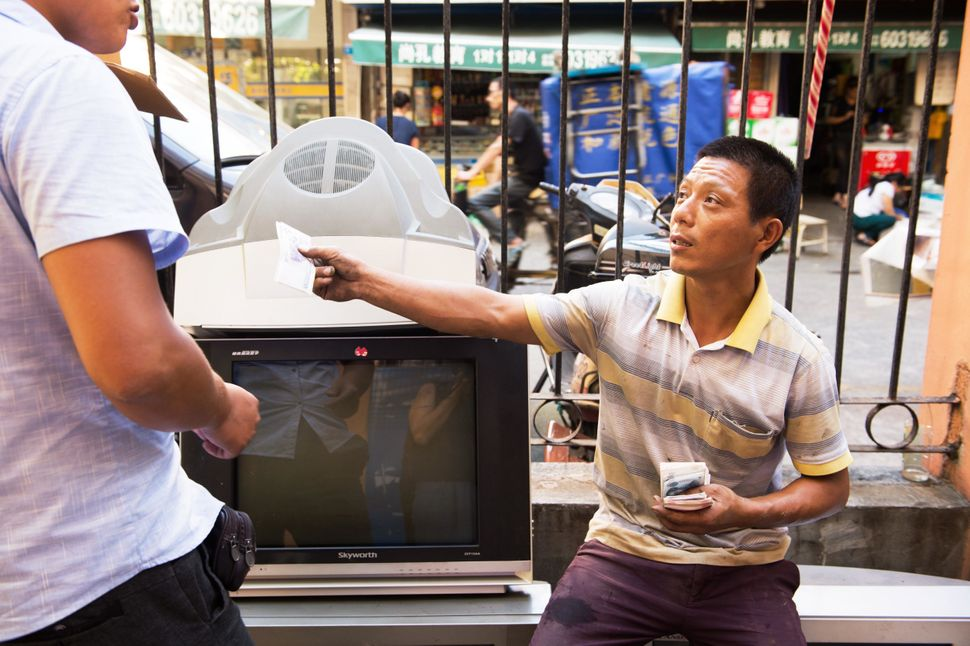 Mr. Wang, an informal recycler, pays another recycler for delivering a washing machine in Shanghai. Recyclers like&