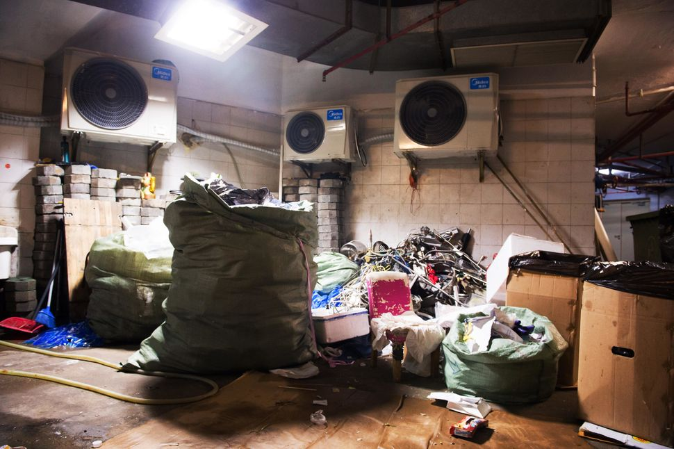 In the basement of a large apartment complex, recyclers sort and stockpile trash -- and live among the detritus.