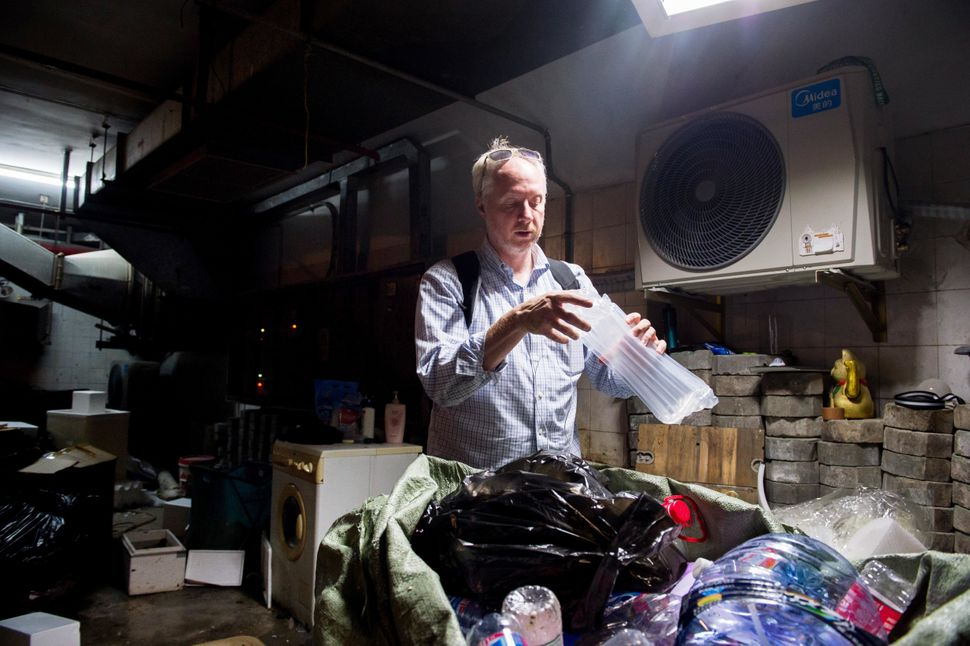 Richard Brubaker, founder of Collective Responsibility, picks up some recyclable waste in the basement of the apartment compl