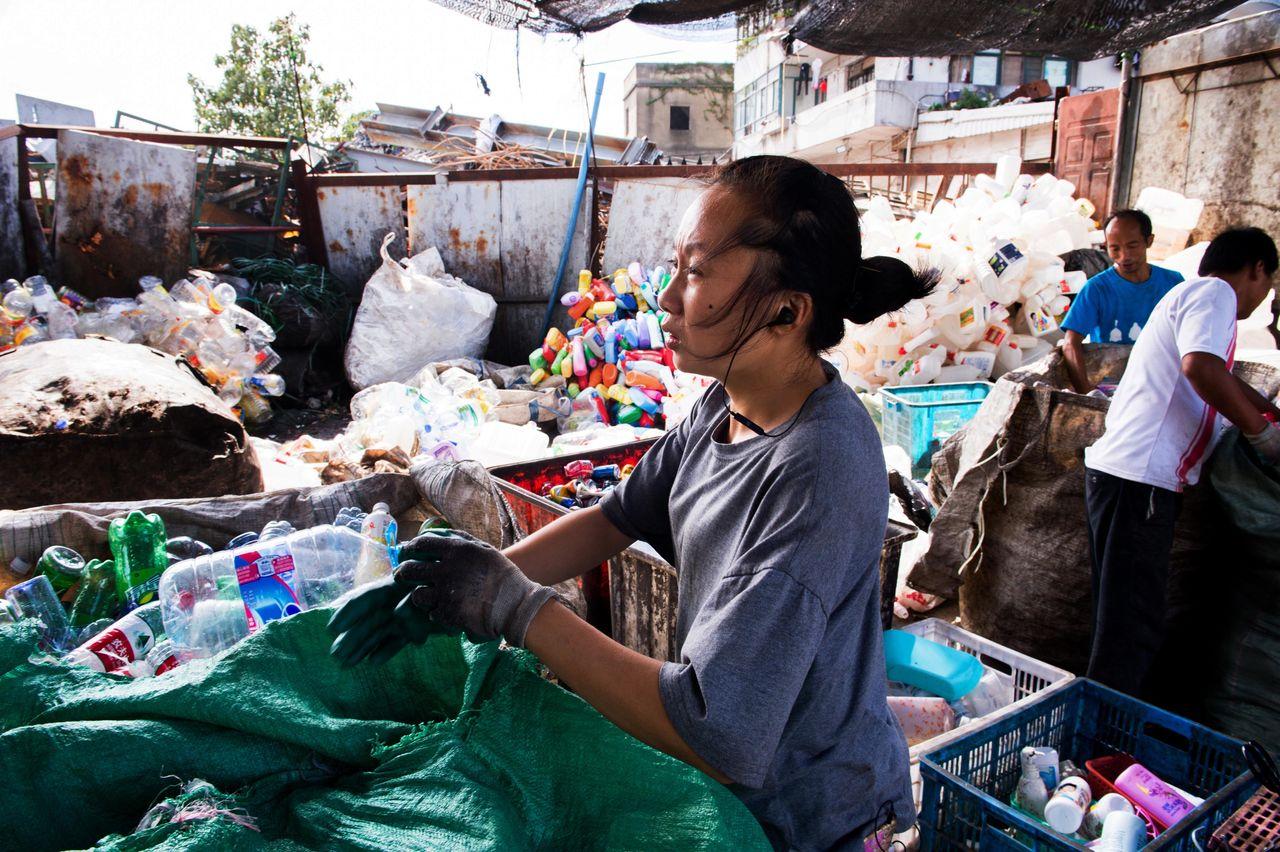 An informal recycler in Shanghai sorting through bags of plastic waste.