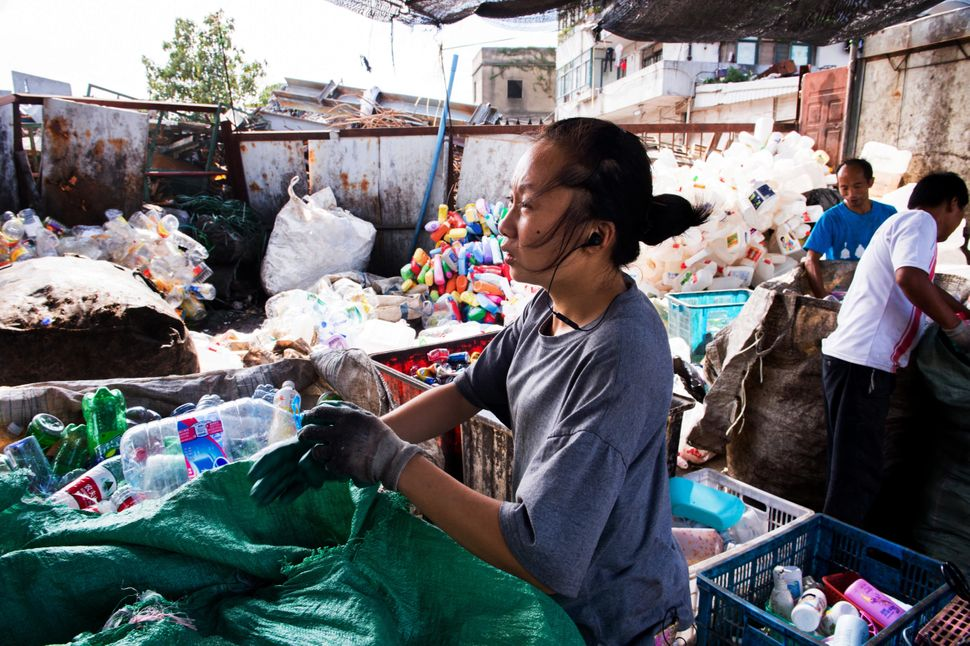 An informal recycler, who said she was from Anhui province, sifts through bags of plastic bottles in Shanghai.