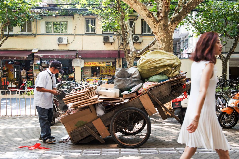 An informal recycler takes a break on a Shanghai walkway.