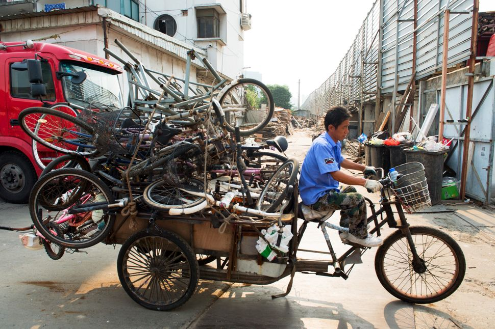 An recycler rides on the streets of Shanghai with a pile of bicycles.