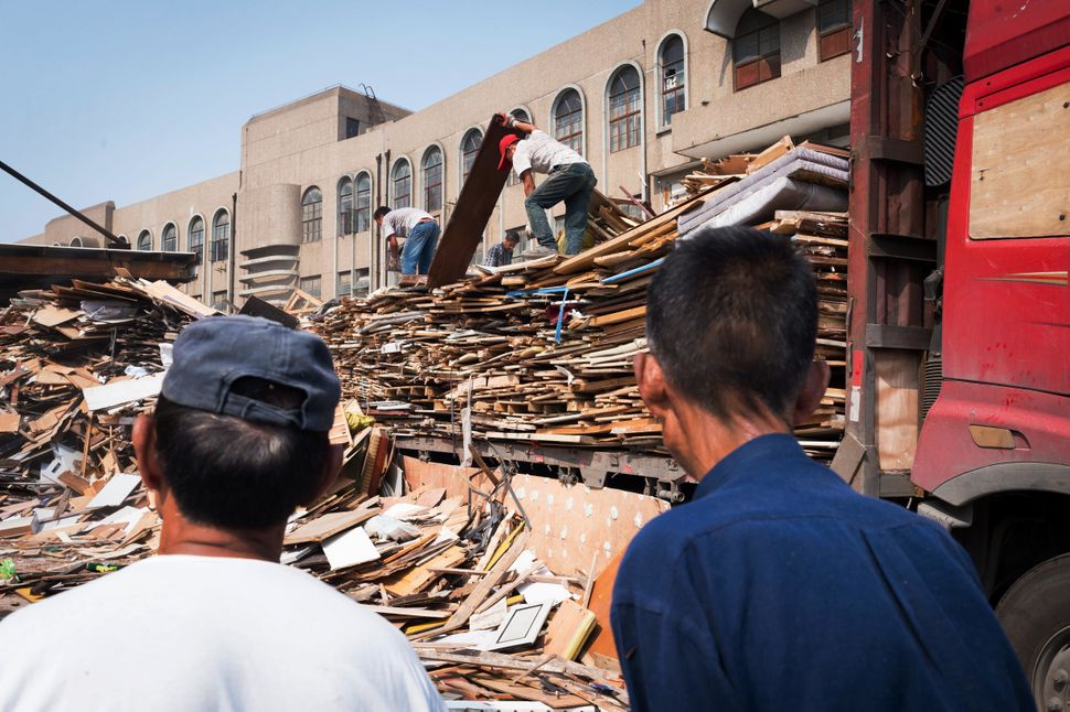 At an informal sorting center in Shanghai, recyclers sift through piles of wood items.