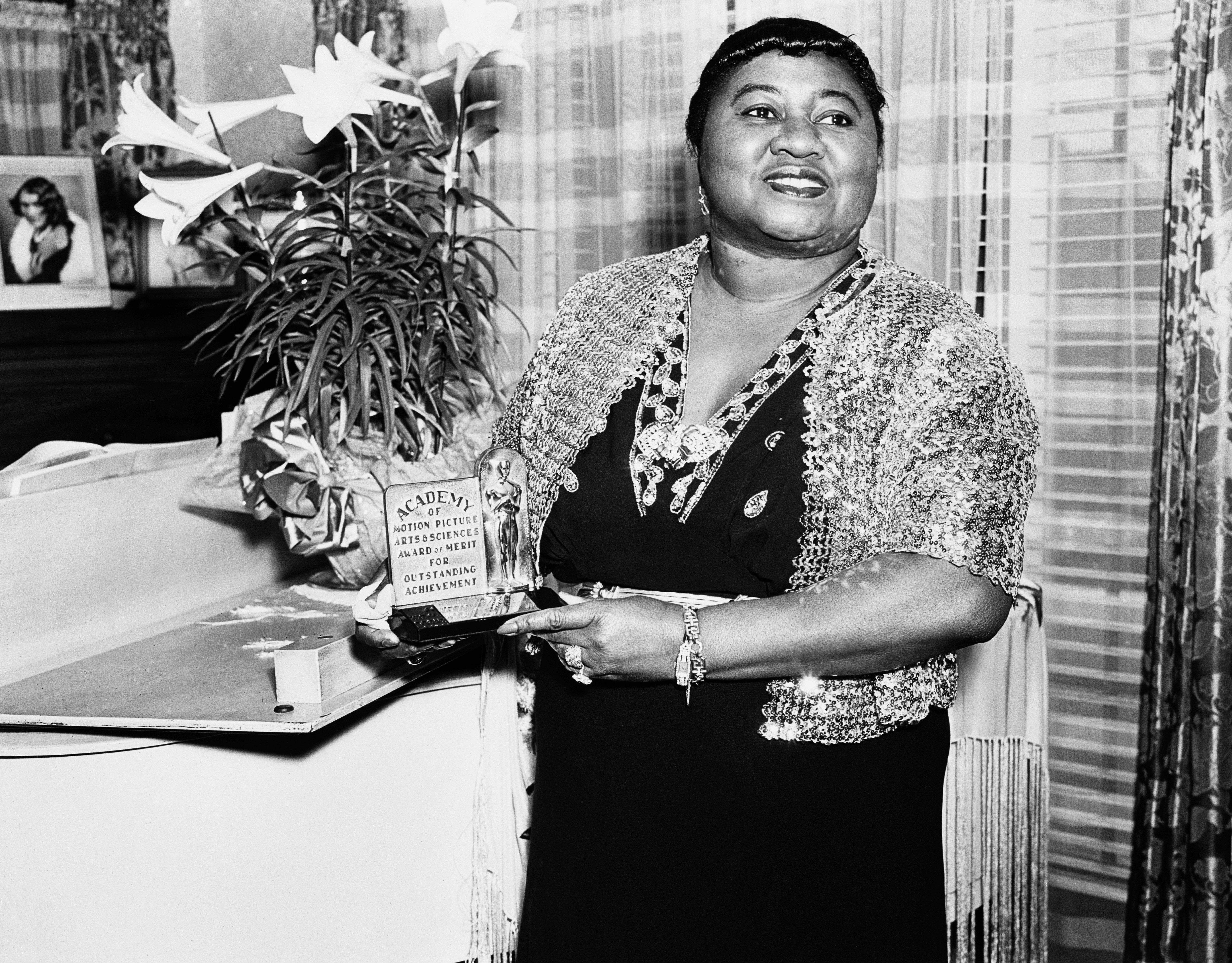 American actress Hattie McDaniel (1895 - 1952) with her Academy Award of Merit for Outstanding Achievement, circa 1945. McDaniel won an Oscar for Best Supporting Actress for her role of Mammy in 'Gone With The Wind', making her the first African-American to win an Academy Award. (Photo via John Kobal Foundation/Getty Images)