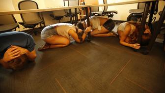 LOS ANGELES, CA - OCTOBER 15: USC Cinema students take cover under their desks during an earthquake drill on October 15, 2015 in Los Angeles California. Students joined 21.5 million people worldwide who took part in safety drills and aftermath and recovery exercises in observance of the eighth annual Great ShakeOut. (Photo by Al Seib/Los Angeles Times via Getty Images)