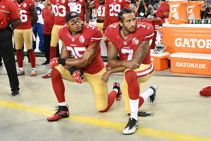 San Francisco 49er Eric Reid kneels beside Colin Kaepernick in protest against police brutality and systemic racism / Th