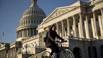 A bicyclist rides past the U.S. Capitol in Washington, D.C., U.S., on Tuesday, Dec. 19, 2017. Congressional Republicans kicked off the final leg of their six-week legislative sprint to overhaul the U.S. tax code and deliver a major policy victory for President Donald Trump before years end. The House is scheduled to vote Tuesday on the tax bill and Senate leaders intend to bring the measure up as soon as they get it. Photographer: Andrew Harrer/Bloomberg via Getty Images