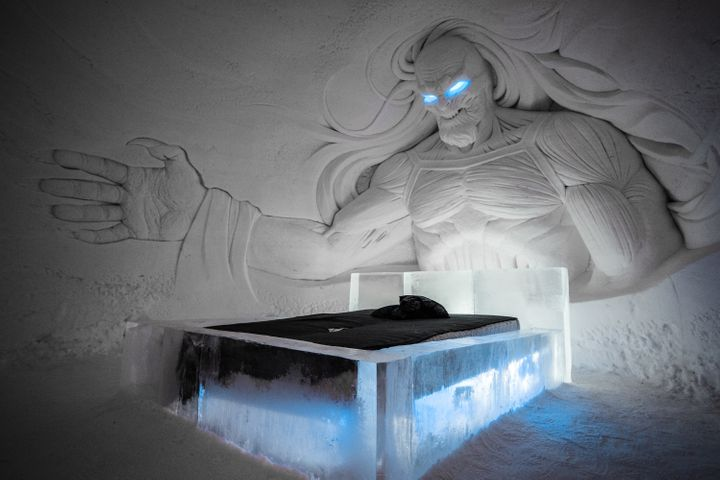 A White Walker sculpted out of ice looks down at a hotel bed inside the Lapland Hotels SnowVillage.