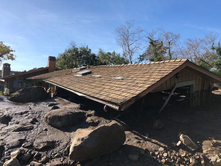 A damaged Montecito house is surrounded by dislodged boulders and debris.