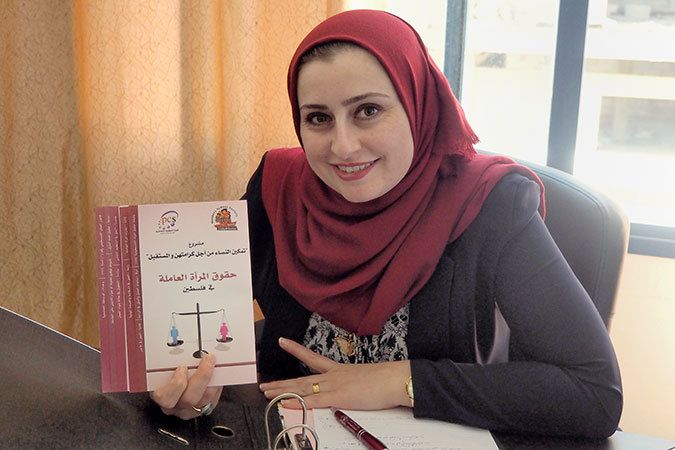 Ayk Sbaihat showing a booklet on Palestinian women's labour rights, produced by the Reconciliation Units of Kannanyat.