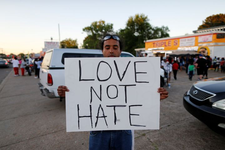 Everett Mathews holds a sign as community members gather for a vigil at the Triple S Food Mart after the U.S. Justice Departm