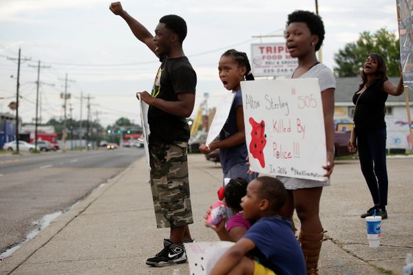 Demonstrators protest the fatal police shooting of Alton Sterling outside the Triple S Food Mart in Baton Rouge, Louisiana.