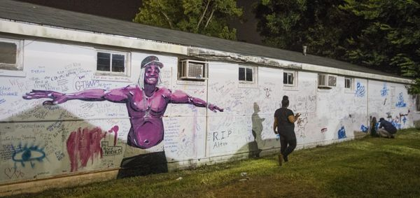 A person reads the personal messages written on the wall next to the convenience store where Alton Sterling was shot and kill