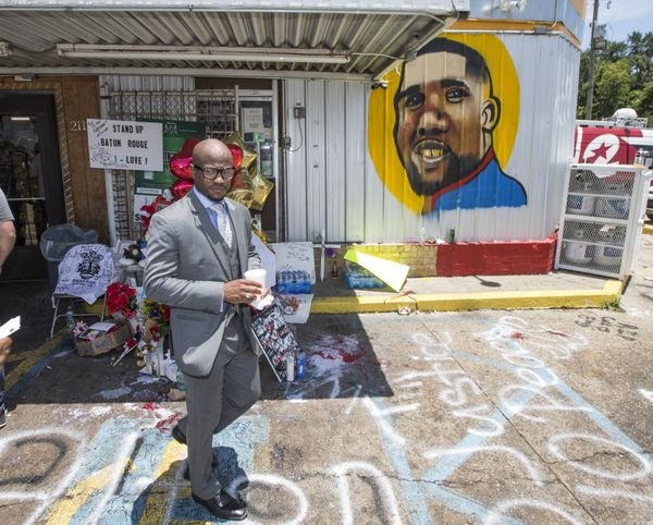 Attorney L. Chris Stewart passes by a memorial for Alton Sterling after speaking to the media in front of the Triple S Mart.